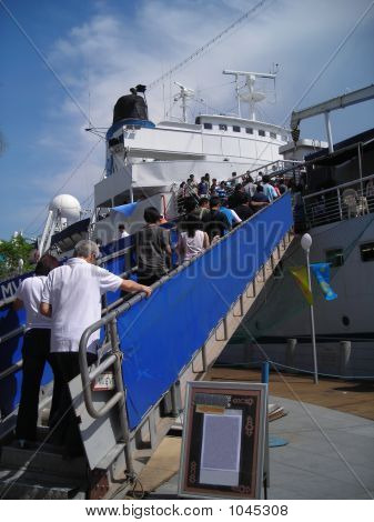 Passengers Boarding A Ship To Go On A Journey