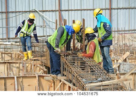 Construction workers fabricating ground beam reinforcement bar