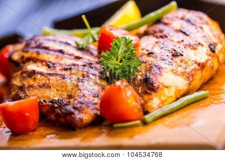 Grilled chicken breast in different variations with cherry tomatoes, green French beans, garlic, her