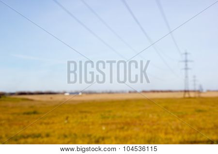 High Voltage Post. High-voltage Tower Sky Background. Power Lines In Field. Bokeh