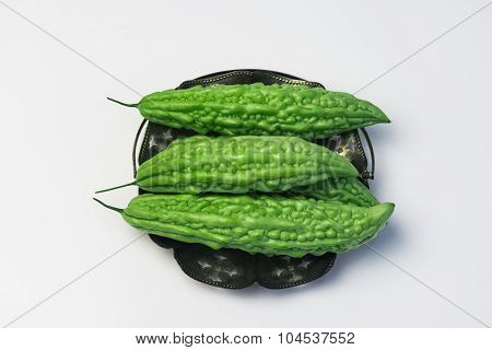 Whole karela bitter melon caraili studio close up white background inside metal basket