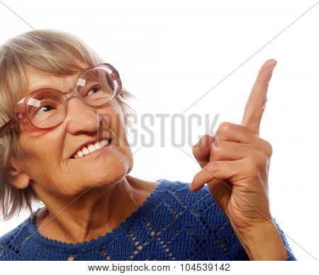 happy senior woman pointing upwards isolated on white background
