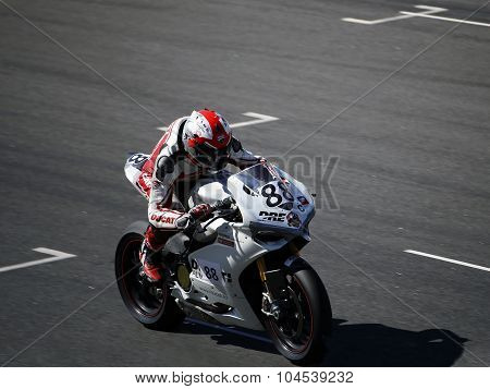 The Racer On A Motorcycle Rides On The Speed Of The Track