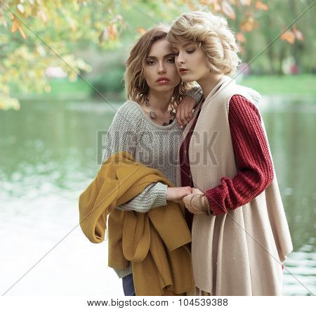 Young beautiful women near lake. Glamour fashion portrait.