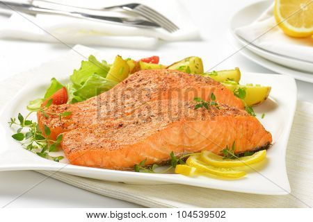 close up of pan fried salmon fillets served with vegetable garnish on white plate and place mat