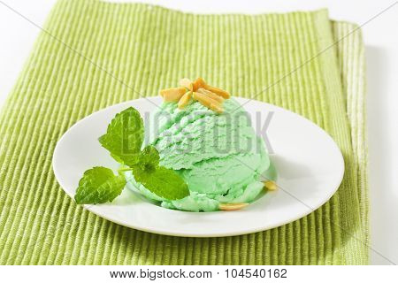 scoop of green ice cream on white plate and green place mat