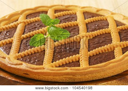 detail of chocolate tart with lattice top on wooden cutting board