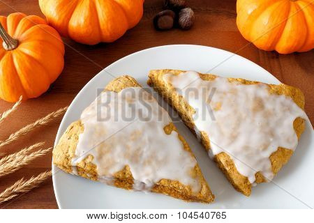 Pumpkin scones with frosting, on plate with wood background
