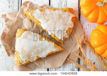 Autumn pumpkin scones with frosting, overhead view on rustic wood