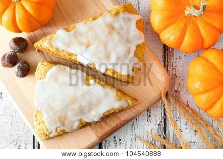 Sweet pumpkin scones with frosting, overhead view on wood