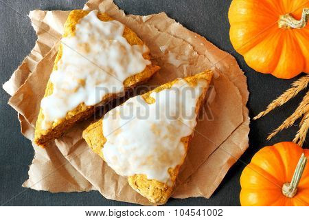 Pumpkin scones with frosting, overhead view on slate background