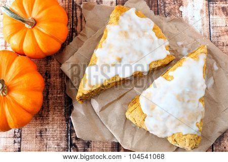Sweet autumn pumpkin scones with frosting on rustic wood