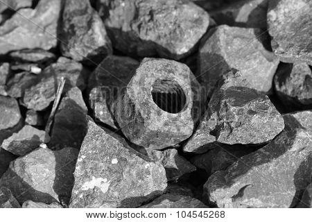 old screw nut between stones