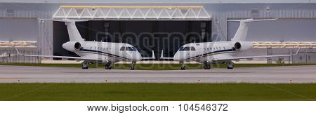 Two private planes in front of a hangar