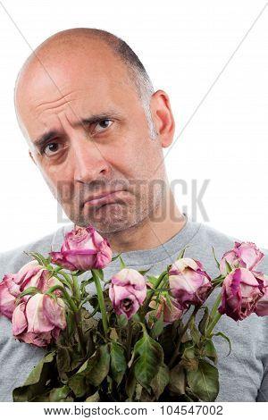 Sad man holding dead flowers