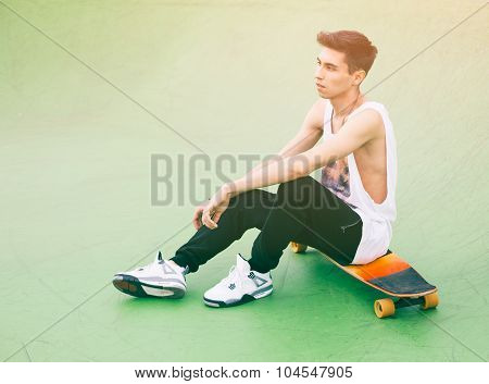 Fashionable young man sitting on a longboard in the ramp for skateboarding in the summer. Sun glare