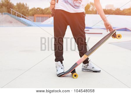 Young man holding a longboard hand on a warm summer evening. Skateboard ramp