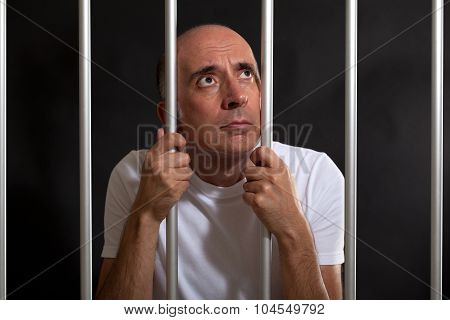 Desperate and sad man behind bars