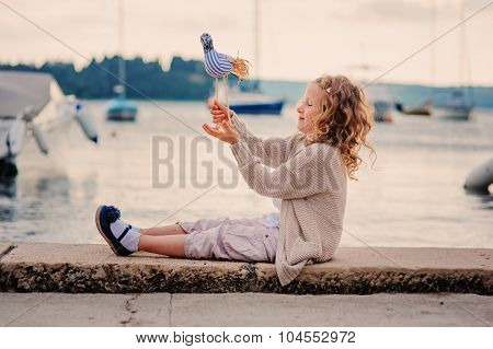 cute happy curly child girl playing with toy bird on seaside on summer vacation