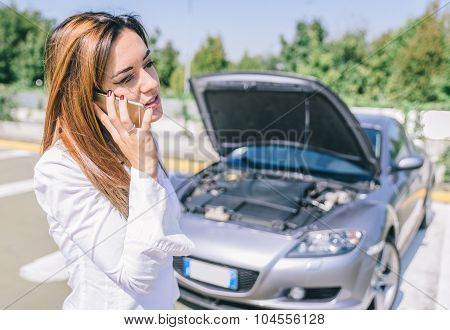 Car Breakdown. Young Woman Calling Assistance On The Phone