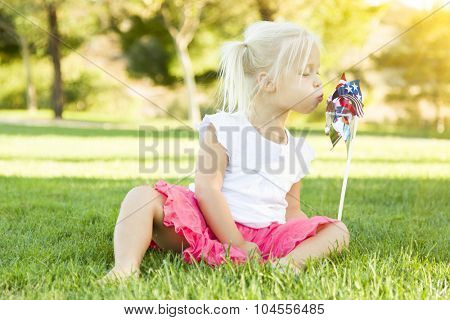 Cute Little Girl Sitting In Grass Blowing On Pinwheel Toy.