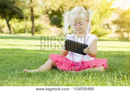 Cute Little Girl Sitting In Grass Playing With Cell Phone.