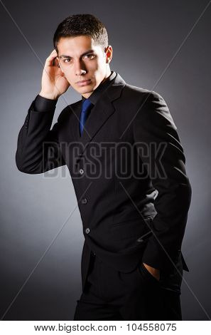 Young elegant man against gray