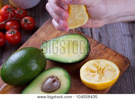 Man hand squeezing lemon on avocado.