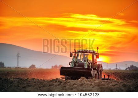 Tractor With Cultivator Handles Field Before Planting, Sunset Shot