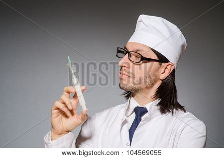 Male doctor holding syringe against gray