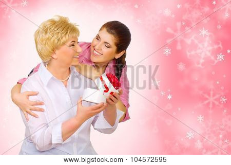 Young woman giving gift to her mother on winter background