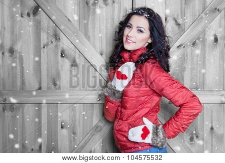 Beautiful  young happy smiling woman wearing winter  jacket and gloves covered with snow flakes. Christmas portrait concept.