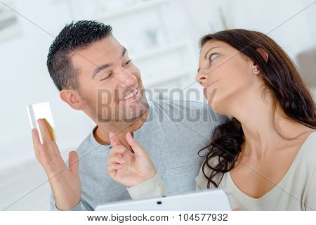 Couple on computer, man holding credit card