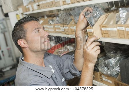 Mechanic choosing spares from stores