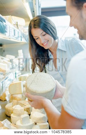 Woman presenting a selection of different cheeses