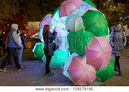 ST. PETERSBURG, RUSSIA - OCTOBER 8, 2015: People watching light installation with umbrellas in the Alexander garden during LumiFest. It was the first festival of light culture in Russia