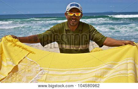 Smiling Brazilian Beach Seller Wearing Sunglasses Selling Blankets