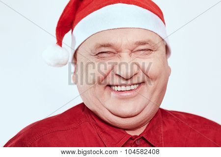 Close up portrait of laughing out loud aged man wearing Santa Claus hat and red shirt against white background - Christmas concept
