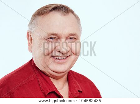 Close up portrait of smiling aged man wearing red shirt against white background - retirement concept