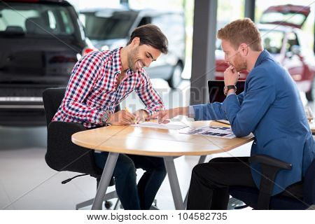Happy man with car dealer buying a car signs the contract in car showroom
