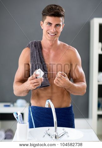 Young man flossing his teeth in front of mirror in bathroom