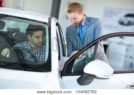 Car agent and customer in car showroom,  together watching the performance of vehicle