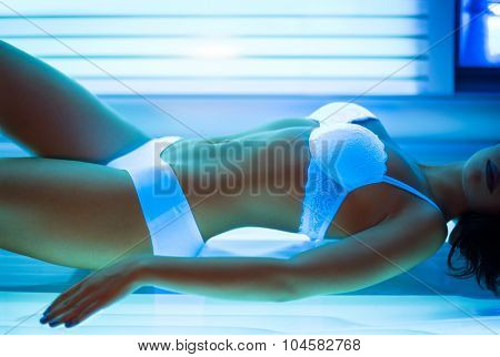 Young fit woman sunbathing in solarium