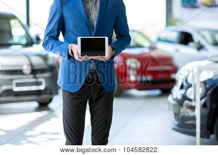 car seller holding empty pc tablet and standing in car in showroom