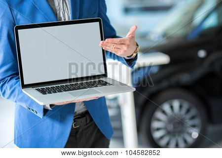 car dealer pointing in the empty screen of the laptop