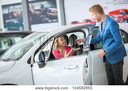 Sales manager giving key from the new car female client
