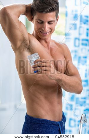 Smiling man front mirror putting antiperspirant on armpit, routine after showering