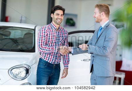 salesman and client at the car saloon, sitting, gesturing and presenting selling conditions