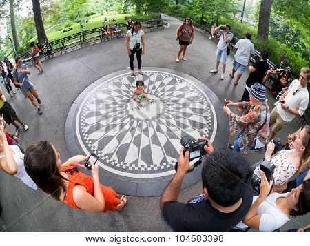 NEW YORK,USA - AUGUST 21,2015 : Small child at the Imagine mosaic commemorating John Lennon at Strawberry Fields in Central Park