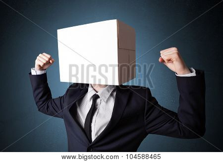Businessman standing and gesturing with a cardboard box on his head